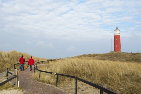 Two man are walking to red lighthouse Stock Photo - 18203555