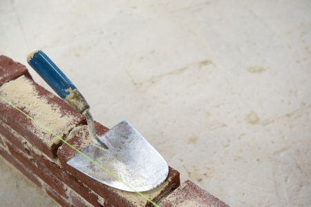 Blue trowel and brick wall with copy space photo