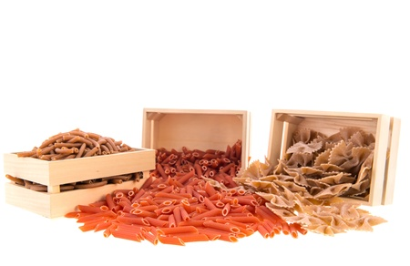 Crates with wholemeal farfalle, macaroni and penne photo