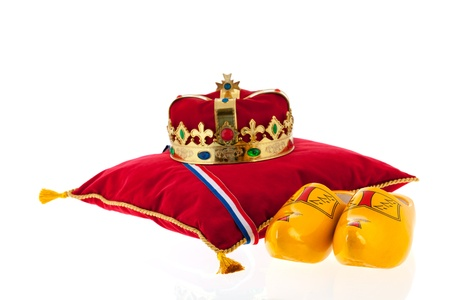 Golden crown on red velvet pillow for coronation in Holland with pair of wooden shoes photo