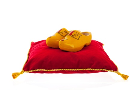 royal red velvet pillow with golden rope and pair of wooden clogs isolated over white background Stock Photo - 18501901