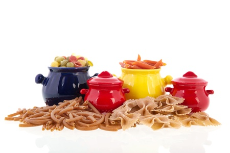 Colorful pots with wholemeal farfalle, shells, macaroni and penne photo