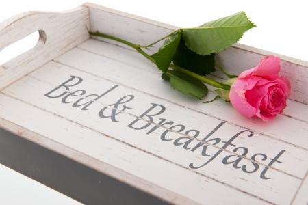 Bandeja de madera para la cama y desayuno con color de rosa se levantó