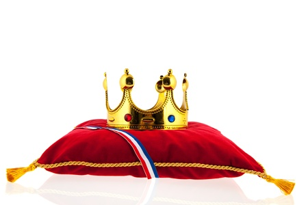 Golden crown on red velvet pillow for coronation in Holland photo