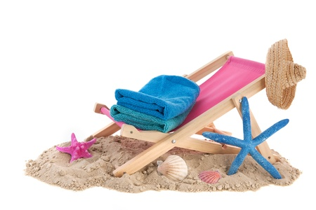 Beach chair with blue towels in the sand photo