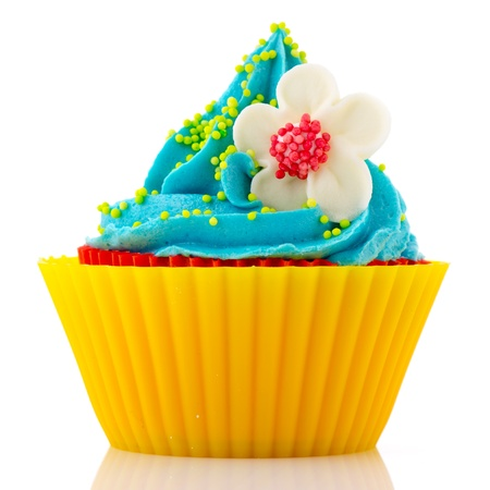 Red and blue birthday cupcake with flower isolated over white background photo