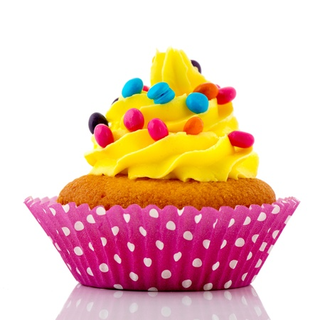 Birthday cupcake with colorful confetti on yellow butter cream photo