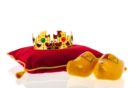 Golden crown on red velvet pillow for coronation in Holland with Dutch wooden clogs photo