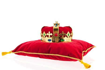 Golden crown on red velvet pillow for coronation photo