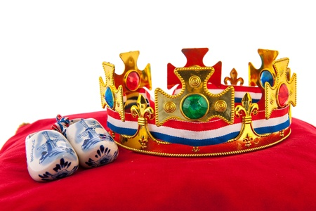 Golden crown on red velvet pillow for coronation with wooden shoes in Holland photo