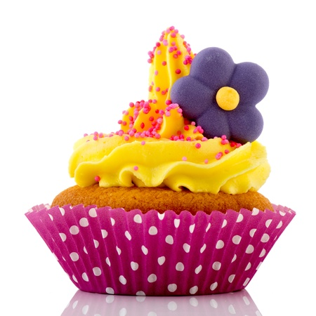 Pink cupcake with flower and yellow buttercream isolated over white background photo
