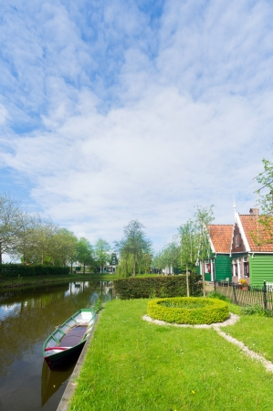 Typical Dutch village with green wooden houses and ditch photo