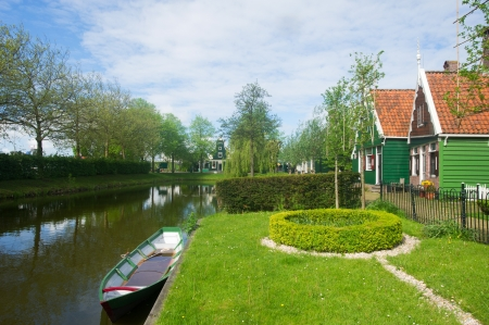 Typical Dutch village with green wooden houses and ditch