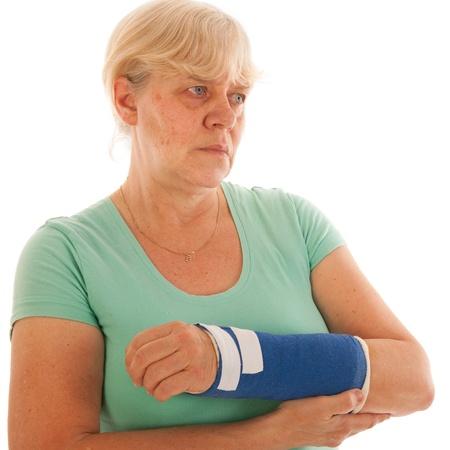 broken wrist: Mujer de edad avanzada con fractura de mu�eca en azul yeso aislado sobre fondo blanco