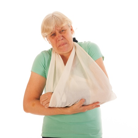 Old woman with broken wrist in blue gypsum isolated over white background photo