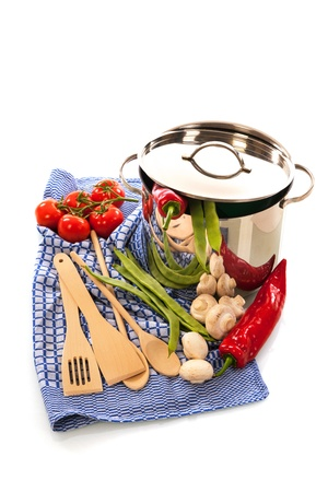 cooking with pan, wooden spoons, cloth and vegetables isolated over white background photo