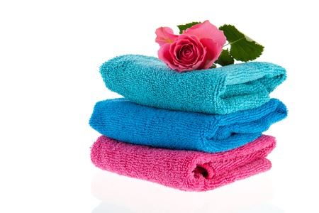Blue and pink towels stacked with pink rose on top photo
