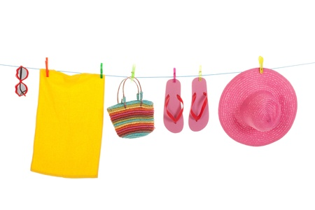 Line with hanging flip flops and pink straw summer hat towel and sunglasses