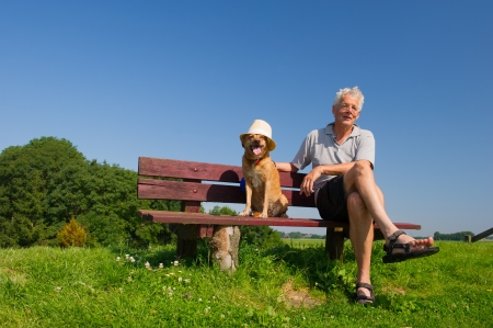 Funny wet dog with hat on bench outdoor with his owner sitting in nature landscape