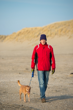 Man walking with dog at the Dutch beach in winter photo
