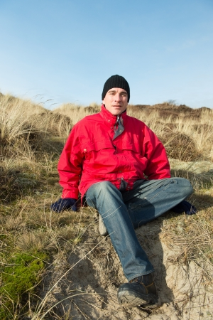 Outdoor man sitting in dunes in winter time photo