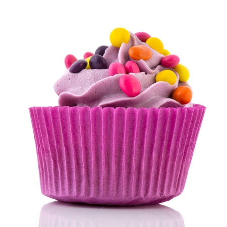 Purple birthday cupcake with confetti isolated over white background photo