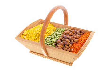 Wooden harvest basket with colorful legumes isolated over white background photo