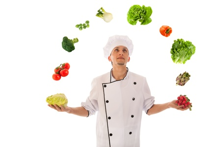 Cook juggling with assortment fresh vegetables isolated over white background photo