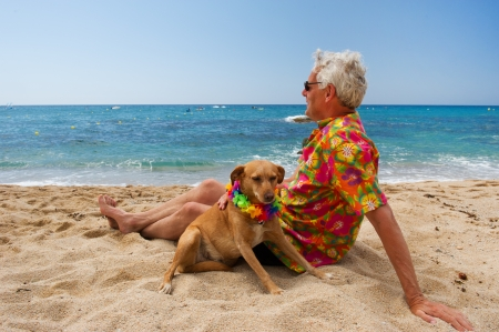 Relaxing elderly man with dog laying at the beach photo