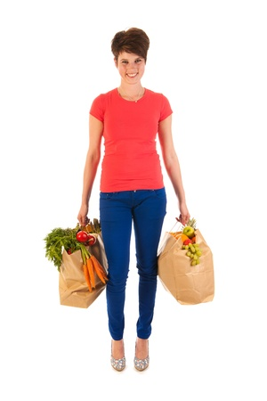 Pretty young woman with heavy bags healthy vegetables and fruit isolated over white background photo