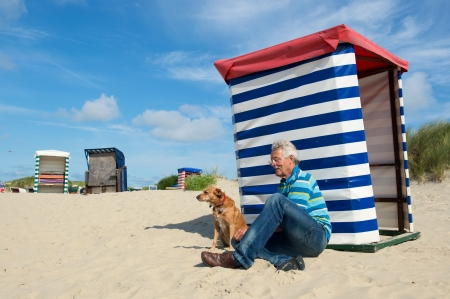Man sitting with dog at the beach of German wadden island with typical striped chair photo