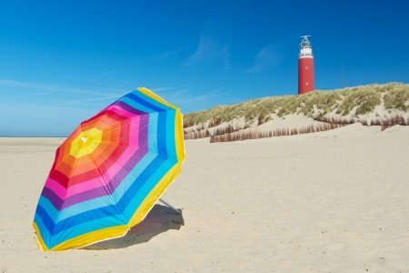 lighthouse and colorful parasol on Dutch wadden island Texel photo