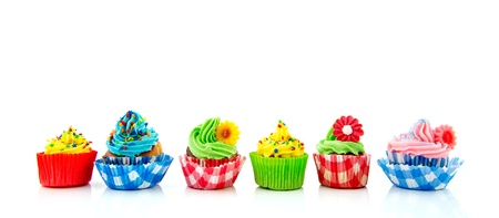 Row with six home made colorful cupcakes with butter cream photo