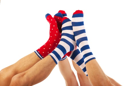 Feet in striped and dotted socks isolated over white background photo