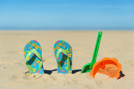 Flip flop and plastic toys at the summer beach photo