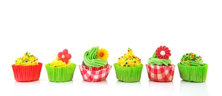 Row green and red cupcakes with butter cream isolated over white background photo