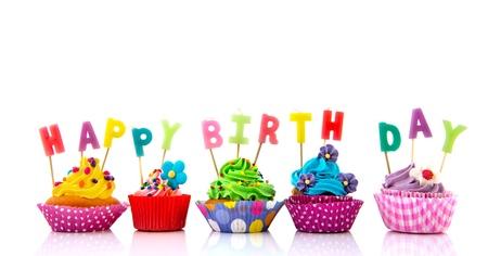 velas cumpleaños: Colorido cupcakes con velas de cumpleaños felices aislados sobre fondo blanco