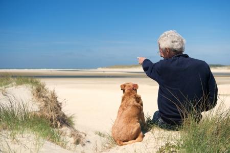 ワッデン テセル島のオランダ浜砂丘上の犬と一緒に座っている男