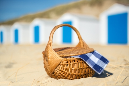 Row blue and white beach cabins and picmic basket with checked napkin photo