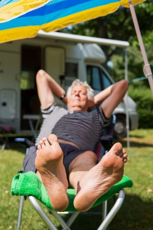 Elderly man is sleeping at the camping with bare feet photo