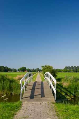 Small wooden white bridge in agricultural landscape photo