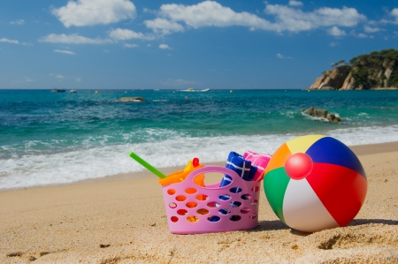Pink beach bag and colorful ball in the sand near the water line at the Spanish beach photo