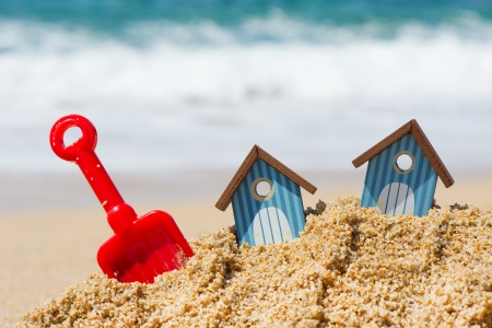 Miniature beach huts with red plastic shovel