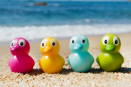 Colorful toy ducks in the sand at the beach photo