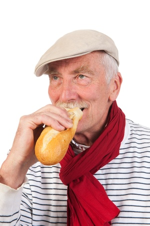 Portrait senior man with cap and scarf eating French bread photo