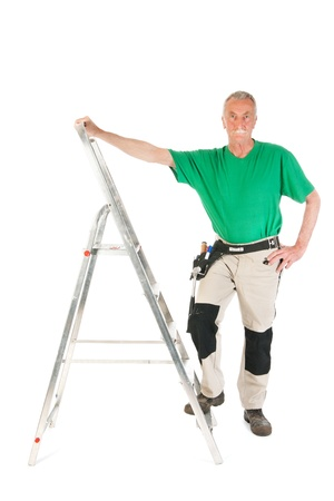 Senior man as manual worker with stepladder isolated over white background photo