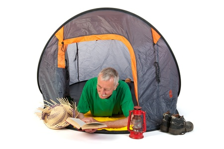 Senior man on vacation and reading laying in tent photo