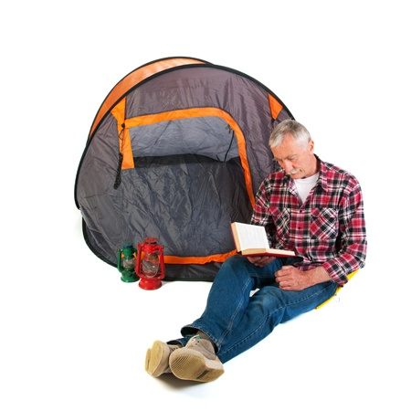 Senior man on vacation and reading by tent photo