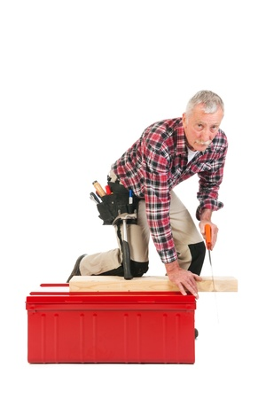 Senior man sawing as manual worker isolated over white background photo