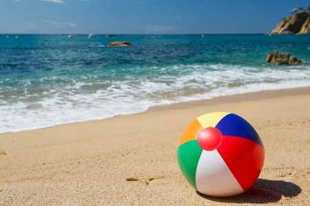 Inflatable beach ball in the sand near the water line at the Spanish beach photo